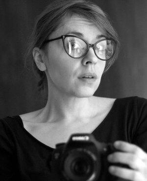 Anna Ciszek ilustratorka Zwierzobytów na zdjęciu trzyma aparat fotograficzny. Twarz skierowana prawym profilem z lekko uniesionymi brwiami znad okularów.